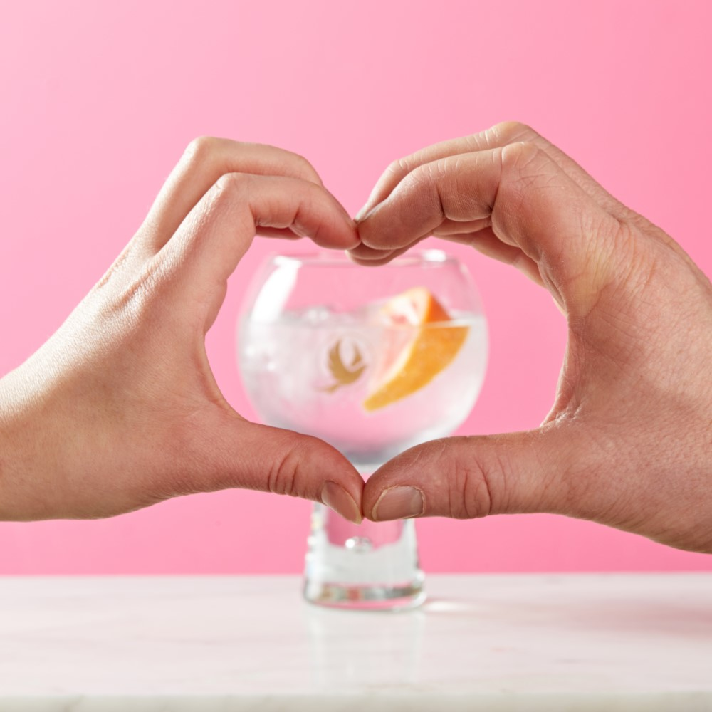 An Amplify and tonic framed by two hands in a heart shape.